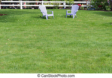 Green lawn with two purple chairs