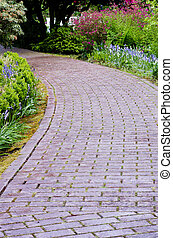 Garden path with flowers blooming - A winding garden path of...
