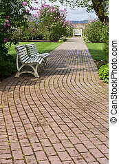 Garden path winding past white benches