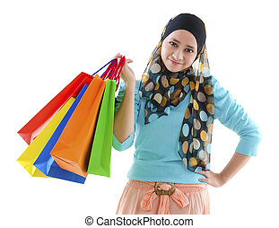 Muslim shopper - Pretty young muslim woman holding shopping...