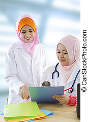 Muslim doctor - Two female Muslim doctor discussing on...