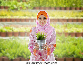 Go Green - Concept of young Muslim girl holding a plant on...