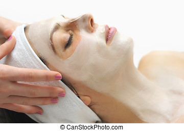 facial mask in a day spa - a woman relaxes during a beauty...