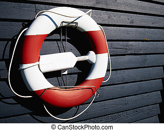 Life buoy preserver ring belt hanged on a dark wooden wall...