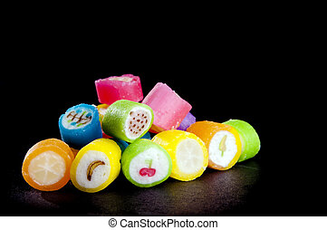 Lollies in different colors with fruit symbols over black in...