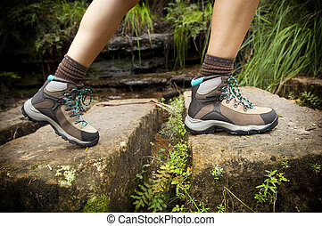 Hiking Boots - Fit young hiker crosses stone steps in hiking...
