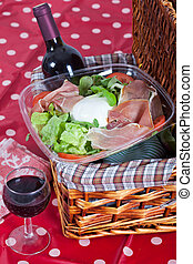 Pic-nic basket with salad and glass of wine