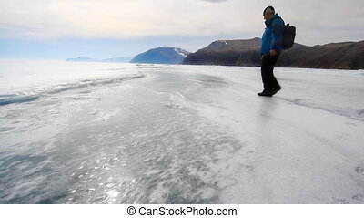 winter lake - man is going on the ice lake