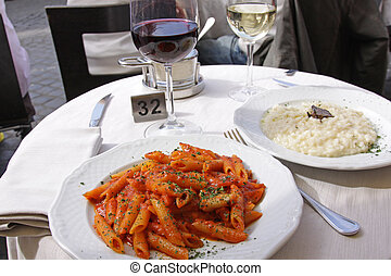 Wine and Pasta Outside - Wine and pasta sitting on table at...