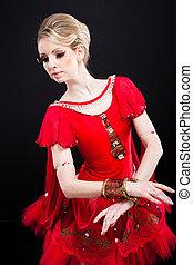 beautiful ballerina wearing red tutu posing on black
