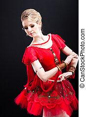 ballerina wearing red tutu posing on black