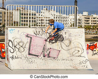 boy rides his scooter at the skate park - boy jumps with his...