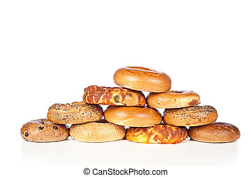 Bagels on white background - A stack of assorted, fresh,...