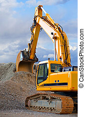 Digger - Yellow digger with big heap of gravel on blue sky