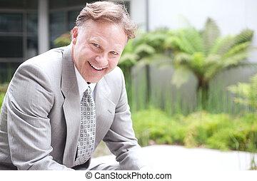 portrait of a confident mature businessman sitting outside...