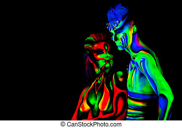 Man and woman with fluorescent bodyart. Black background....