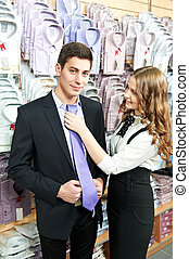 man and assistant at apparel clothes shopping - Young man...