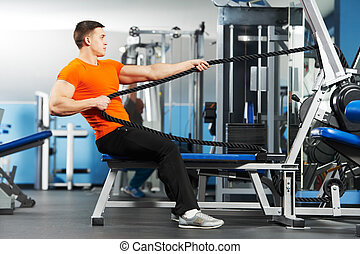 bodybuilder man doing exercises in fitness club - Smiling...
