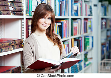 young adult student selecting book in library - young...