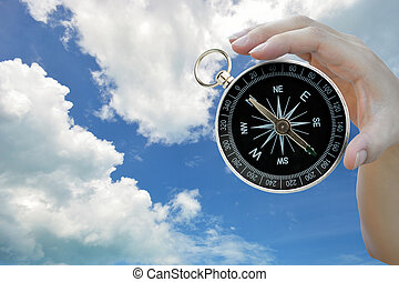 Compass - Classic compass in lady hand on sky background.