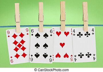 playing cards hung on clothesline - four playing cards hung...
