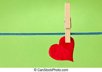 red heart hung over a green background - red paper heart...
