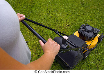 Grass cutting - Woman mowing lawn, focus on mower