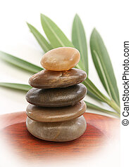 Balancing stones with leaves and white background