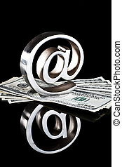 At symbol on money - At symbol paperweight on a pile of 100...
