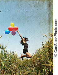 Young woman with colorful balloons. Photo in old color image...