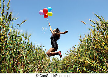 Young woman holding colorful balloons and flying over a...