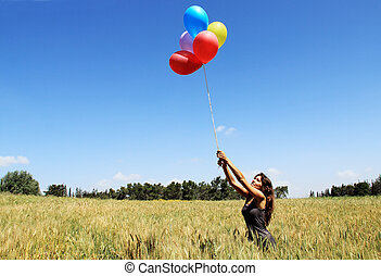 Young woman with colorful balloons in the field
