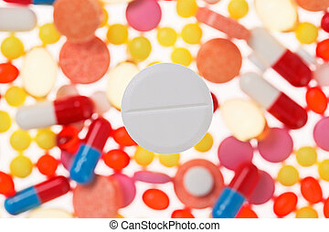 One big tablet (pill) macro view on blurred multicolored drugs background, medical concept
