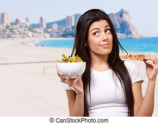 portrait of young woman choosing pizza or salad against a...