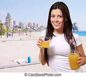 portrait of young girl drinking orange juice against a beach