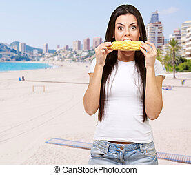 portrait of young woman eating corn cob against the beach
