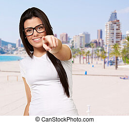 portrait of young woman pointing with finger against a beach