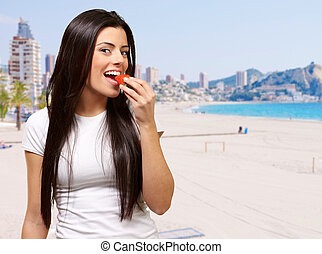 portrait of young woman eating strawberry against a beach