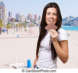 portrait of young woman eating chocolate bar against a beach