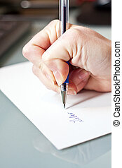 womans hand is writing a letter with a pen