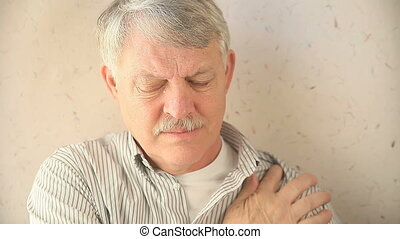 man rubs sore shoulder