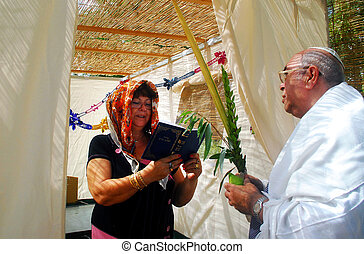 Praying in Sukkah for Jewish Holiday Sukkot - A Jewish man...