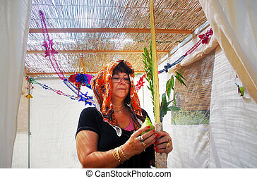 Praying in Sukkah for Jewish Holiday Sukkot - A Jewish woman...