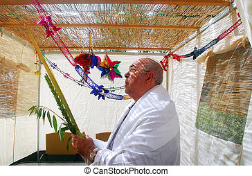 Praying in Sukkah for Jewish Holiday Sukkot - Jewish man...