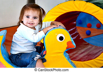 Concept Photo - Childhood - A baby girl has fun and plays in...
