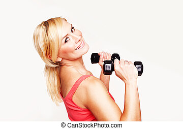 Gorgeous young woman working out with hand weights to keep...