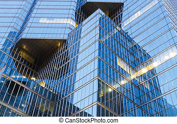 Dynamic - Evening shot of modern office tower with a blue...