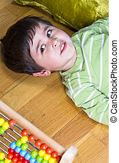 Happy little boy playing with colorful abacus, studio shot