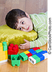 Cute little brunette child is playing with toys while sitting on wooden floor