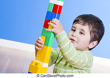 A happy little boy is building a colorful toy block tower